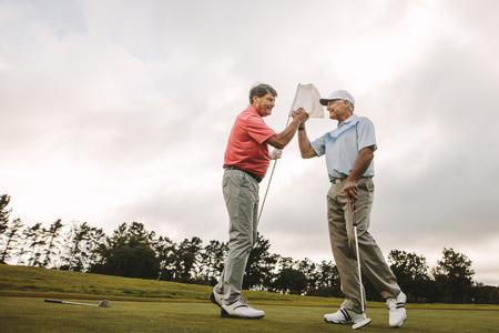 Zwei ältere Freunde, die nach dem Spiel auf dem Golfplatz die Hände schütteln. Professionelle Golfspieler, die das Spiel auf dem Feld genießen.