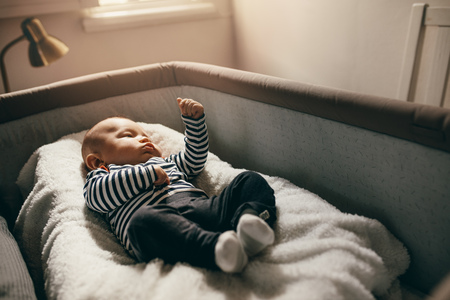 Baby lying in a bedside bassinet moving his hands. Infant lying in a crib at home with sunlight falling on him.