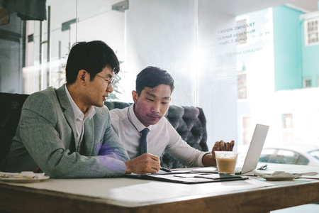 Two asian business men working together in a coffee shop. Business colleagues sitting at coffee shop table analysing some documents. Stock Photo
