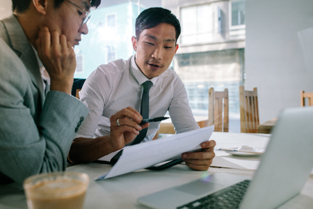 Young asian businessman explaining a document to his manager sitting at cafe table. Business professionals discussing over some paperwork at coffee shop.