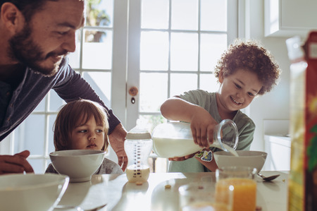 Man watching his kid pour milk in his breakfast bowl. Father and kids sitting at the table preparing breakfast. 스톡 콘텐츠