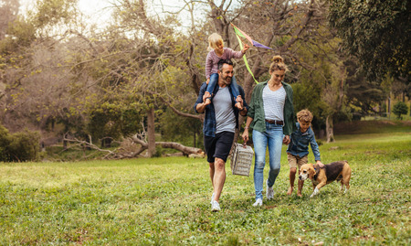Happy couple with their two children and dog walking in park. Man carrying little girl with kite on shoulders and woman carrying a picnic basket with son and pet dog.