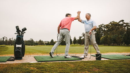 Senior golfers high five at driving range.