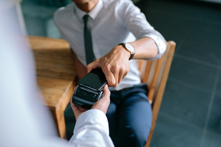 Man paying bill through mobile phone using NFC technology. Closeup of male hand holding his mobile phone over a card reader machine for doing the payment in restaurant.