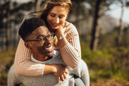 Man giving piggyback ride to hiss girlfriend outdoors. Romantic couple enjoying themselves outdoors.