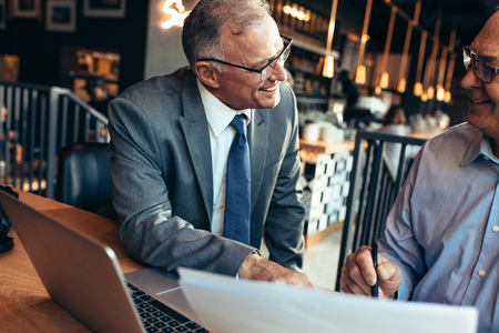 Senior businessman talking with male partner while sitting at a modern coffee shop. Two senior businessman working together on a business report.