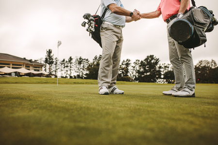 Two senior men shaking hands and when meeting on a golf course. Senior golfers at the golf course greeting each other with a handshake.