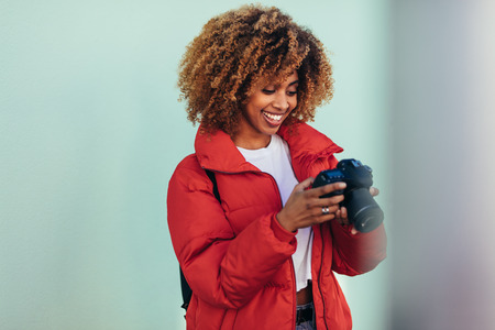 Smiling afro american woman on vacation looking at her camera after taking a photo. Female tourist taking photos standing outdoors. 版權商用圖片
