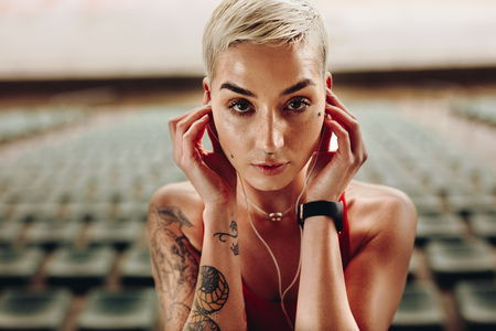 Portrait of a fitness woman standing in a stadium. Close up of a woman having tattoo on body listening to music using earphones. 스톡 콘텐츠