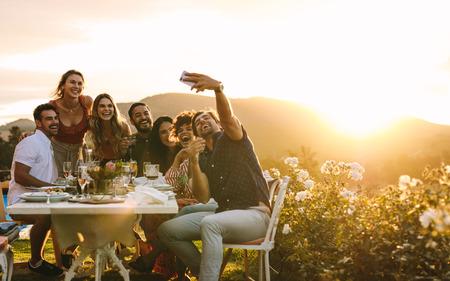 Amici che si rilassano fuori prendendo selfie di gruppo e sorridendo. Ridere i giovani seduti attorno a un tavolo da pranzo all'aperto e scattare selfie. Archivio Fotografico