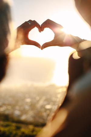 Cerca de la joven pareja de enamorados haciendo un corazón con los dedos a la luz del sol. Pareja romántica haciendo un gesto con un corazón de dedo. Foto de archivo