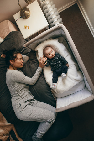 Mother and child sleeping on bed at home. Woman sleeping on bed holding the hand of her baby sleeping in a bedside crib. Stock Photo