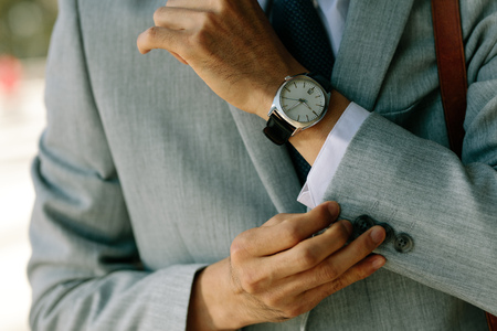 Businessman buttoning his cuffs. Cropped shot of business professional buttoning up his blazer sleeves.