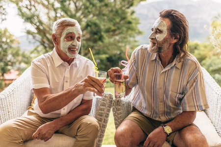 Two elderly friends with facial clay mask on clinking juice glasses. Senior men sitting on chair with spa face mask having juice.