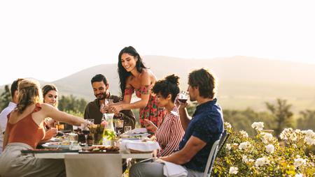 Donna che serve cibo agli amici a cena. Gruppo di giovani che cenano insieme all'aperto.