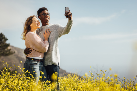 Loving young couple on summer vacation taking a self portrait with smartphone outdoors. Relaxed young couple on holiday taking selfie standing in meadow of yellow flowers.