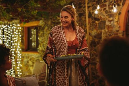 Donna sorridente che serve cibo agli amici a cena. Ospite di una festa che serve cibo agli amici durante una festa di notte.