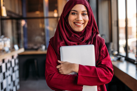Portrait of happy young woman wearing hijab holding laptop computer looking at camera and smiling at cafe. Stock fotó