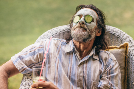 Bearded elderly man sitting on chair with clay mask and cucumber slice on face. 스톡 콘텐츠