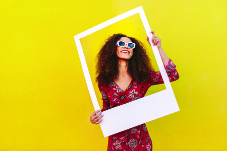 Pretty woman in a red dress and sunglasses standing against a yellow wall and holding a large empty frame. Stockfoto