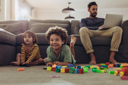 Smiling kids playing with building blocks and watching television at home.