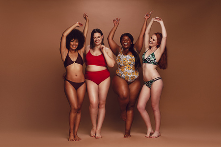 Full length of different size women in bikinis dancing together over brown background. Multi-ethnic women in swimwear enjoying themselves. Stock Photo