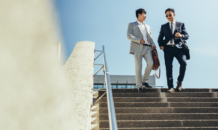 Two business partners walking together down stairs in the city. Korean business men walking down the steps and talking.