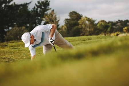 Senior golfer placing the ball on the sand bunker for making his shot. Pro golfer playing on the golf course. Фото со стока