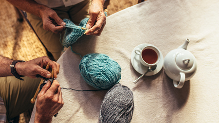 Top view of senior men hands knitting with teapot and teacup on table. Close up of retired men hands with knitting needles and wool yarns. 스톡 콘텐츠
