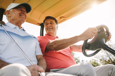 Low angle shot of two senior men driving in a golf cart. Two male golfers in a cart enjoying a round of golf on a sunny day. Stok Fotoğraf