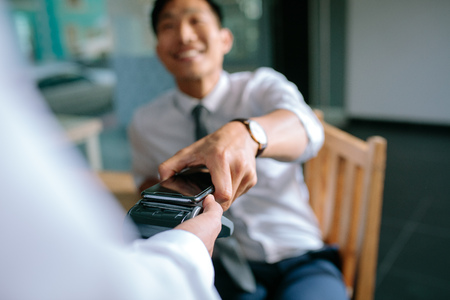 Businessman paying bill through smartphone using NFC technology in restaurant. Closeup of male hand holding his mobile phone over a card reader machine for doing the payment. 写真素材