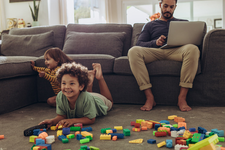 Man working on laptop sitting at home with kids playing on the floor. Cheerful kids playing with building blocks and watching television at home.
