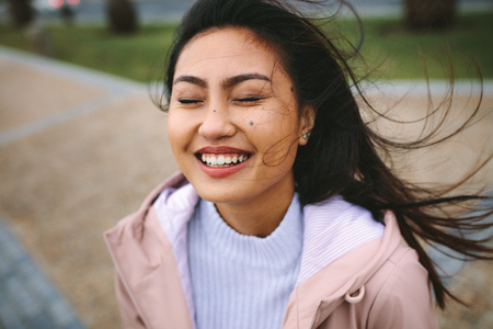 Smiling woman standing outdoors enjoying the breeze with her eyes closed. Portrait of a woman standing outdoors with her hair flying. Reklamní fotografie