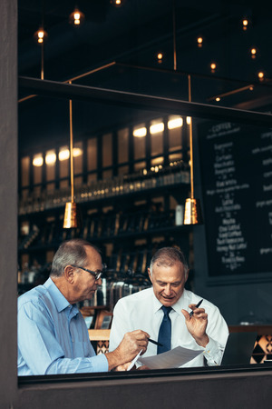 Vertical shot of two senior men meeting in a pub and discussing over a document. Stock Photo