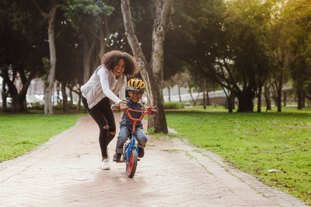 Cute boy learning to ride a bicycle with his mother. Woman teaching son to ride bicycle at park. Stock Photo