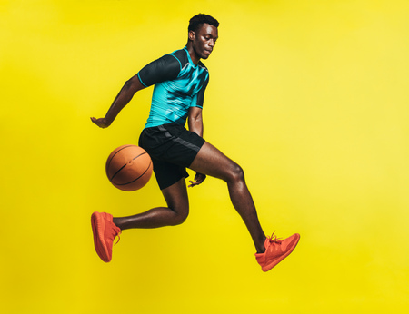Young basketball player dribbling a ball over yellow background. Man in sportswear practicing basketball. Imagens