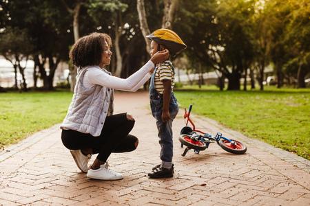 Mujer joven poniendo casco a chico lindo, con ciclo acostado en la parte de atrás en el parque.