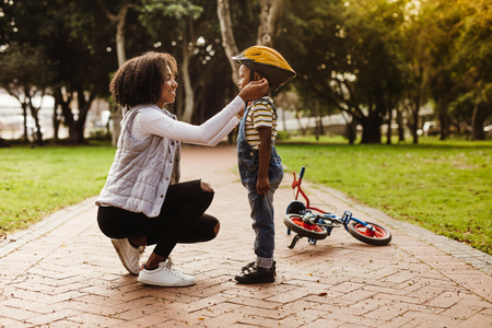 Young woman putting helmet on cute boy, with cycle lying at the back in park.