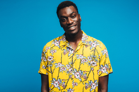 Portrait of african man wearing a Hawaiian style floral shirt and looking at camera.