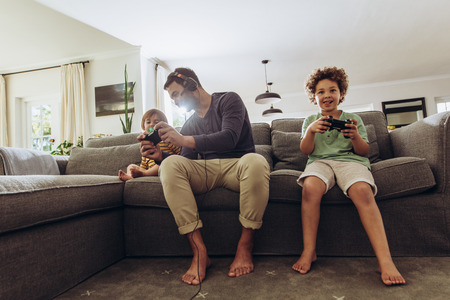 Happy man having fun with his kids playing video game at home. Father playing video game sitting on couch with his two kids. Banco de Imagens
