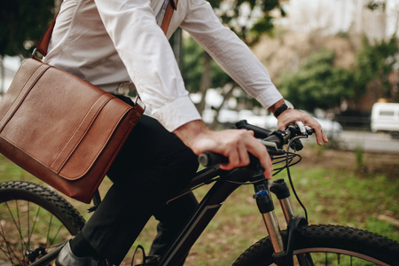Man wearing an office bag riding a bike. Businessman going to office on a bicycle.