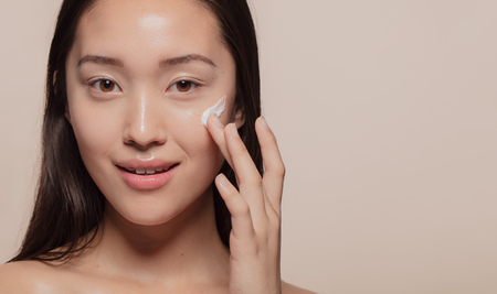 Close up of a asian woman applying moisturizer to her pretty face. Female model putting cream on her glowing face skin. Banco de Imagens