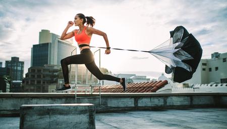 Atleta femminile che si allena sulla terrazza di un edificio con un paracadute legato dietro di lei. Donna fitness che corre forte con un paracadute di trascinamento sul tetto con il bagliore del sole sullo sfondo.
