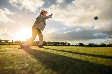 Man playing boules in a playground with sun flare in the background. Old man in hat throwing a boules in a lawn.