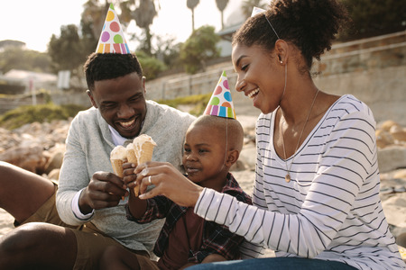 African family with party hats eating ice cream on the beach. Man and woman with son enjoying eating ice-cream. Family enjoying sons birthday with ice cream outdoors.