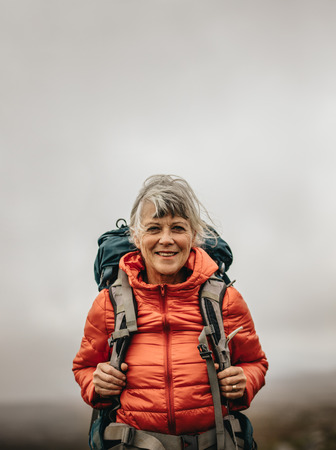 Smiling woman hiker wearing jacket and backpack on a hiking trip. Adventure seeking woman walking on a hill on a cloudy day. Stock fotó - 118801562