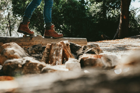Low angle view of a person walking on a fallen tree trunk in a forest. Cropped shot of a person wearing leather shoes walking in forest.