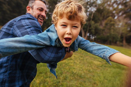 Son with his father having fun in park. Happy boy playing with dad outdoors. Little boy lifted by his father. Banco de Imagens