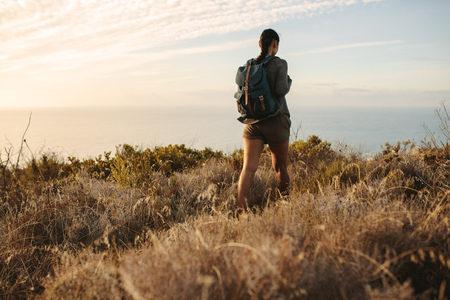 Rear view of woman walking on a mountain trail. Woman walking on a countryside rocky hill with a backpack. Banco de Imagens