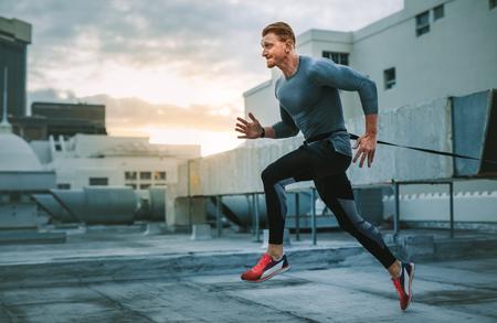 Uomo di forma fisica che corre sulla terrazza di un edificio con una fascia di resistenza alla vita. Uomo che fa allenamento sul tetto facendo corsa di resistenza.